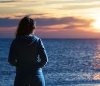 Back of young pensive woman standing by the sea at sunset